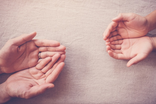 Praying hands of child and adult, compassion donation, charity, helping hands concept Premium Photo