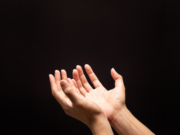 Praying hands in the dark background with faith in religion and belief in god. Premium Photo