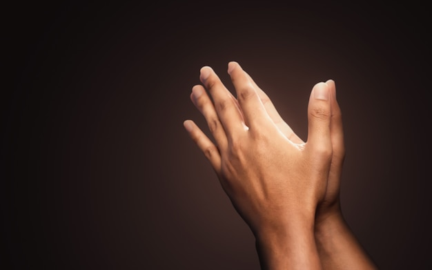 Praying hands with faith in religion and belief in god on dark background Premium Photo