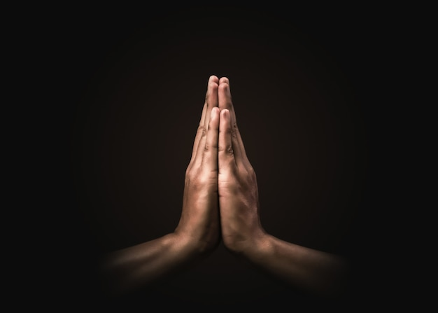 Praying hands with faith in religion and belief in god on dark . power of hope or love and devotion. namaste or namaskar hands gesture. prayer position. Premium Photo