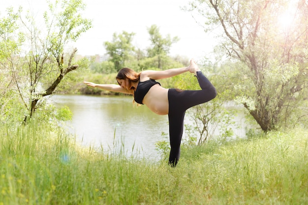 Pregnant beautiful woman yoga outdoors on the grass in sunny summer day Premium Photo