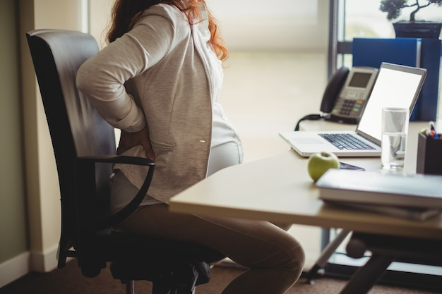 Pregnant businesswoman holding her back while sitting on chair Free Photo