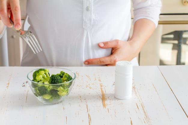 Pregnant female choosing broccoli over vitamins Premium Photo
