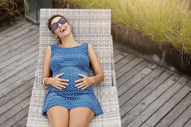 Беременная женщина в стильных солнцезащитных очках и синем летнем платье, лежа на шезлонге, держа руки на животе и счастливо смеясь, наслаждаясь спокойными и мирными днями своей беременности на открытом воздухе Бесплатные Фотографии