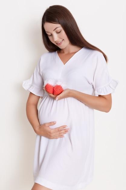 Счастливая беременная женщина держит в руках красные вязаные детские туфли, касаясь живота очаровательной улыбкой Бесплатные Фотографии