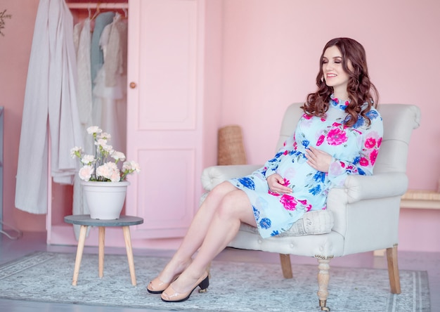 Pregnant happy woman sits in an armchair Premium Photo