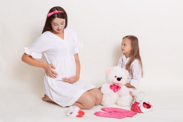 妊娠中の母親と娘が一緒に楽しんで 無料写真