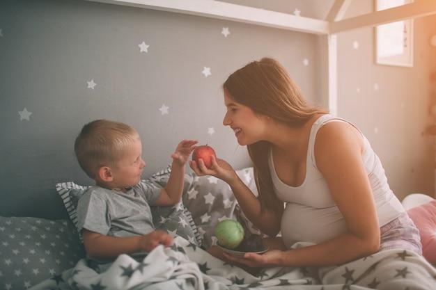 妊娠中の母親と小さな男の子の息子は、午前中に自宅のベッドでリンゴと桃を食べています。寝室でのカジュアルなライフスタイル。 Premium写真