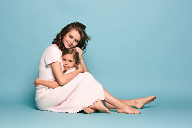 Беременная мать с дочерью подростка. семейный студийный портрет над синей стеной Бесплатные Фотографии