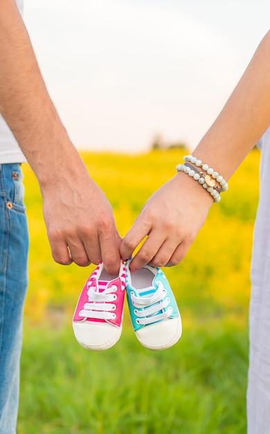 Беременная женщина и мужчина держат детскую обувь. Premium Фотографии