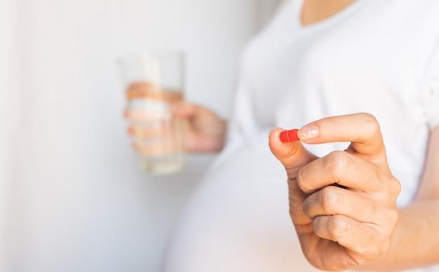 Беременная женщина принимает и ест витаминные лекарства и пьет воду, чтобы питать беременность. концепция здравоохранения образ жизни. Premium Фотографии