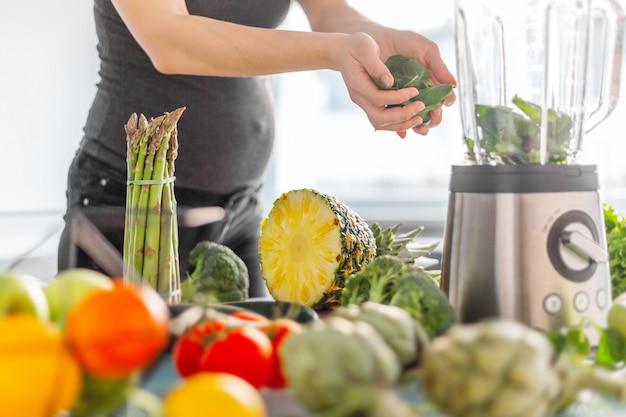 Pregnant woman cooking healthy smoothie Premium Photo