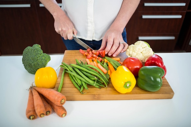 Pregnant woman cutting vegetables in the kitchen Premium Photo
