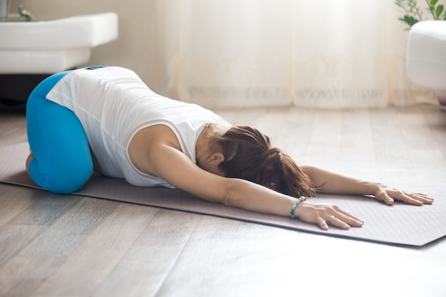 Pregnant woman doing prenatal child yoga pose at home