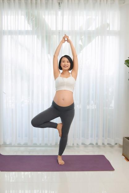 妊娠中の女性がリビングルームでヨガをやって Premium写真