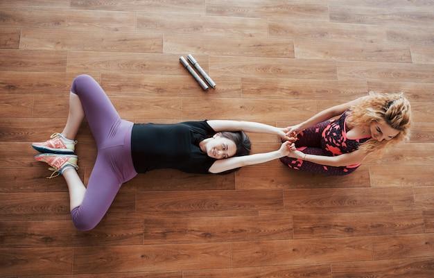 妊娠中の女性はパーソナルトレーナーとヨガをやっています。 無料写真