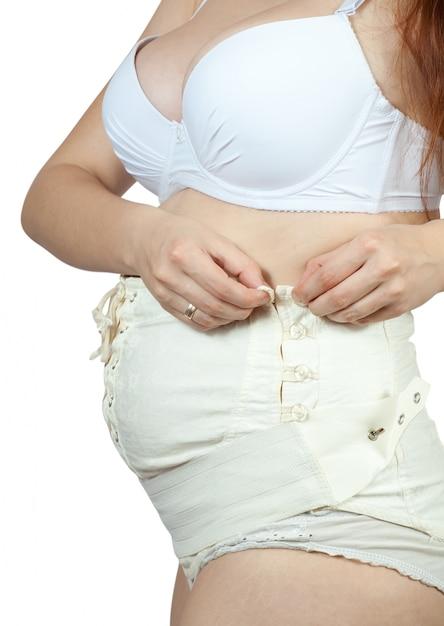 Pregnant woman dressing maternity belt Free Photo