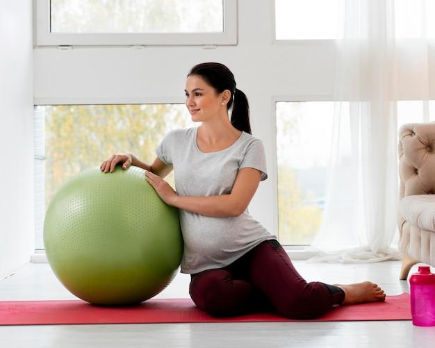 Donna incinta che si esercita con la palla verde di forma fisica Foto Gratuite