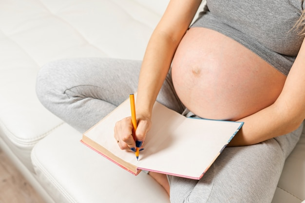 Pregnant woman hands writing something on a book Premium Photo