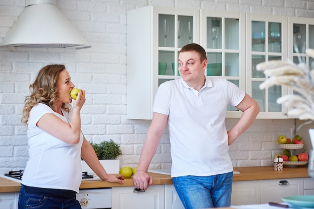 Pregnant woman and her husband in the kitchen at home with fruit. Premium Photo