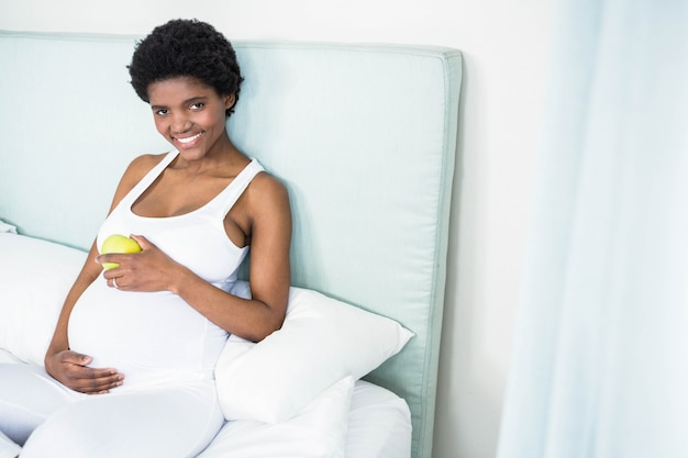 Pregnant woman holding an apple lying on her bed Premium Photo