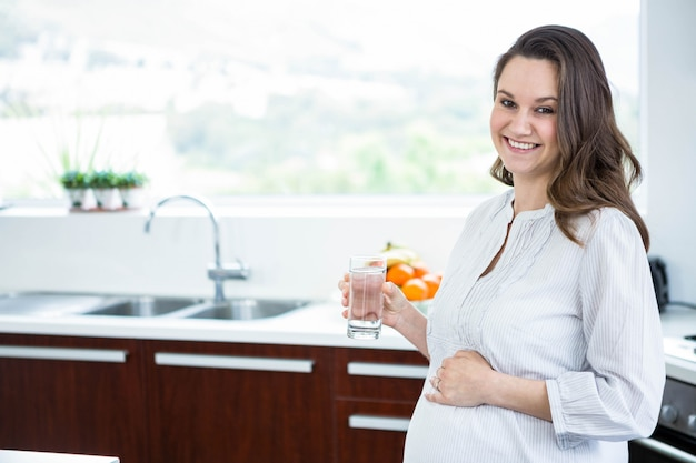 Pregnant woman holding a glass of water in kitchen Premium Photo