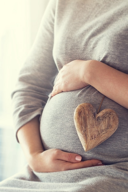Pregnant woman holding a heart while touching her belly Free Photo