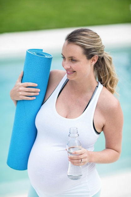 Pregnant woman holding water bottle and mat next to the swimming pool Premium Photo