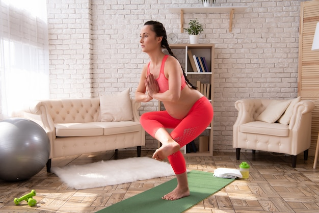 Pregnant woman is doing yoga and meditates at home Premium Photo