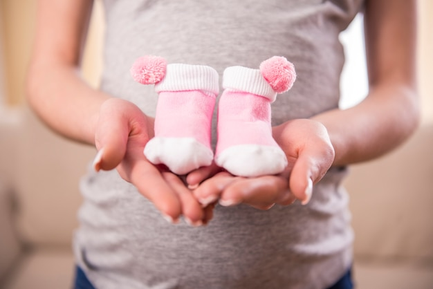 Pregnant woman is holding belly on little socks for babies. Premium Photo