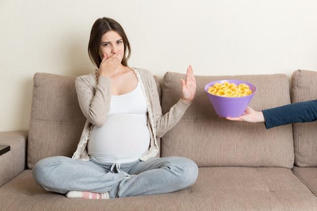 Беременная женщина на диване отказывается есть нездоровые закуски Premium Фотографии