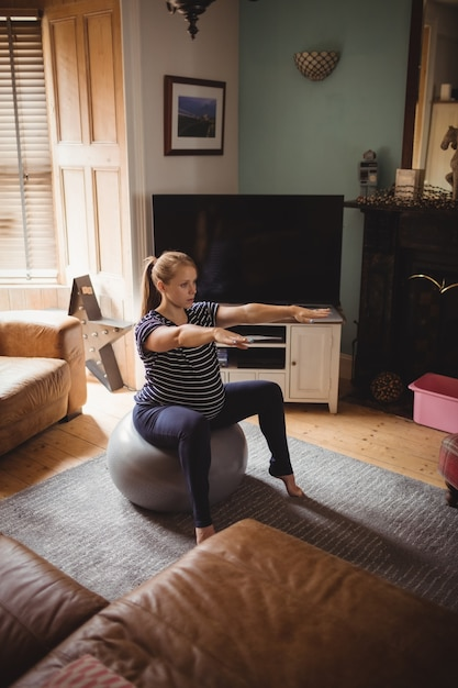 Pregnant woman performing stretching exercise on fitness ball in living room Free Photo