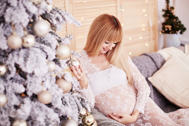 Pregnant woman portrait, new year vibes. charming blonde expecting woman sits Free Photo