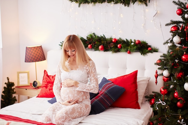 Pregnant woman portrait, new year vibes. charming blonde expecting woman Free Photo