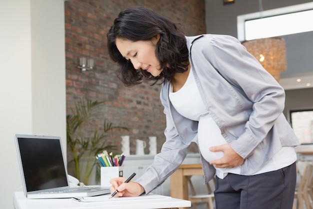 Pregnant woman reading documents at home Premium Photo
