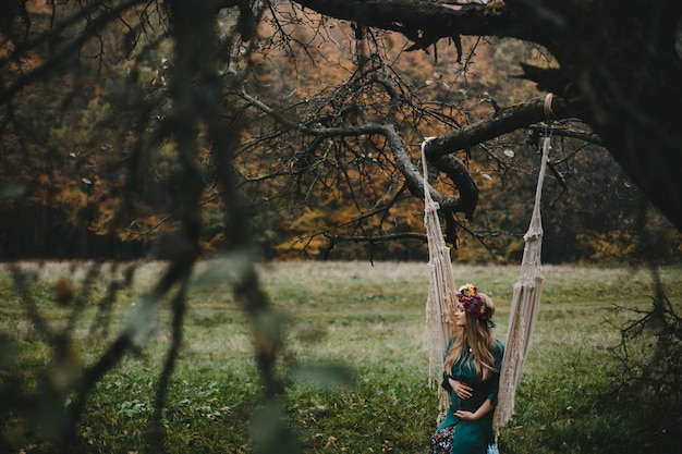 Pregnant woman rests outside on the rope swing hanging Free Photo