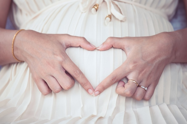 Pregnant Woman Sitting And Making Hand Heart Shape On Her -5306