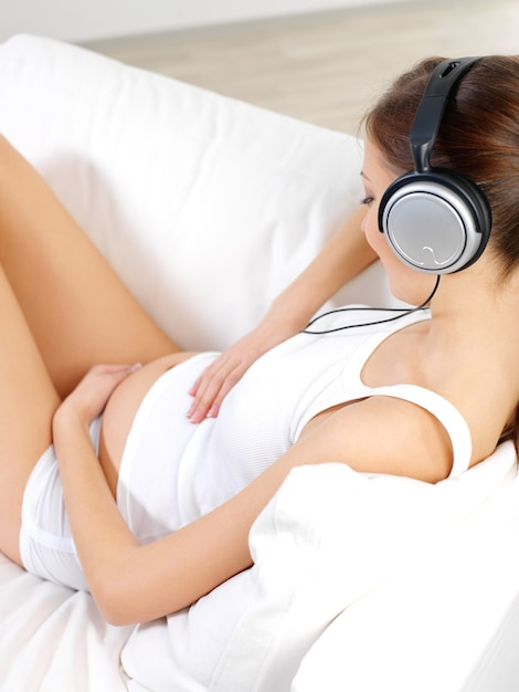 Pregnant woman sitting on white sofa at home and listening music in headphones Free Photo