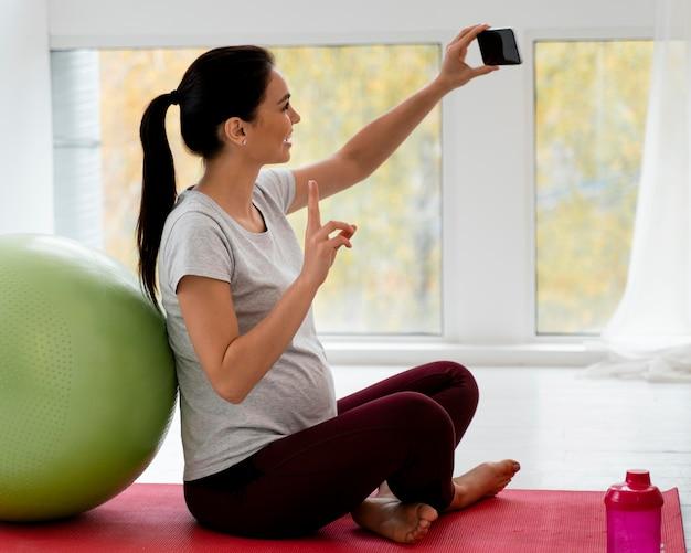 フィットネスボールの横で自分撮りをしている妊婦 無料写真