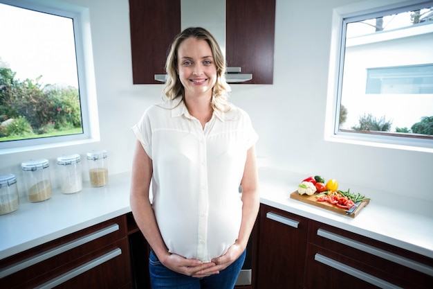 Pregnant woman touching belly in the kitchen Premium Photo
