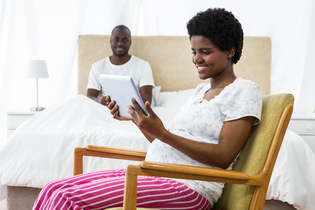 Pregnant woman using digital tablet on chair and man sitting on bed in background Premium Photo