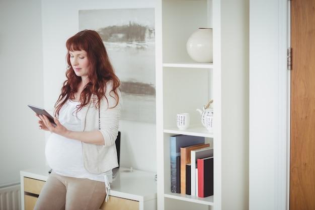 Donna incinta utilizzando la tavoletta digitale in sala studio Foto Gratuite
