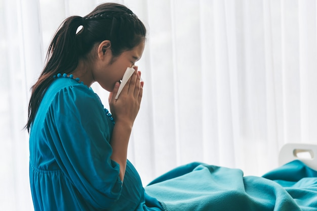 Pregnant woman using a paper towel to wipe the snot  because of the flu. Premium Photo