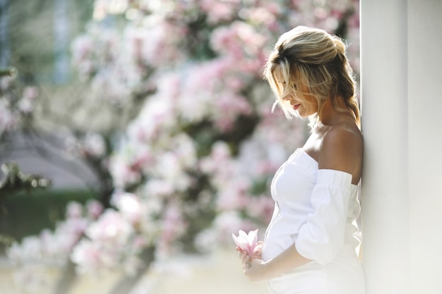 Pregnant woman in a white dress standing near the wall Free Photo