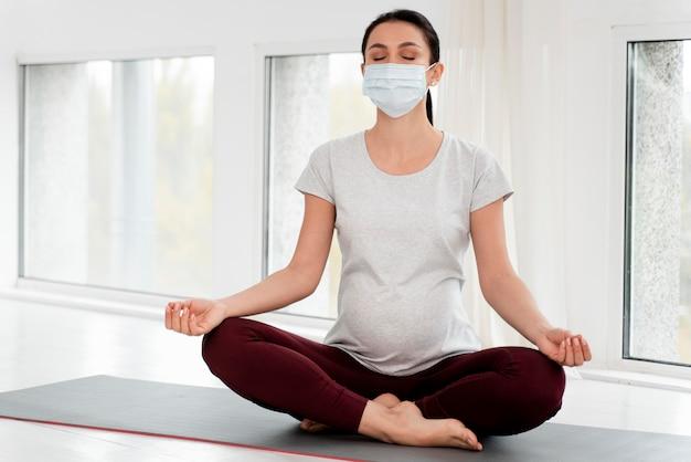 Donna incinta con maschera medica meditando Foto Gratuite