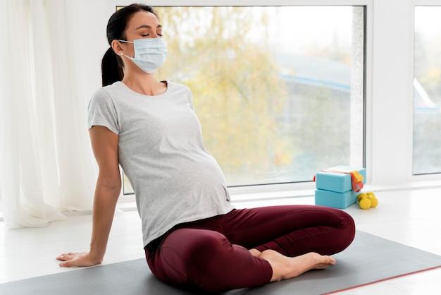 Беременная женщина с расслабляющей медицинской маской Бесплатные Фотографии