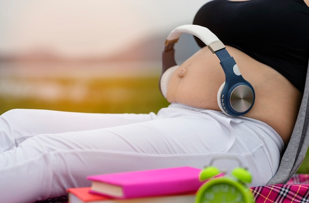 Pregnant women open a song to the stomach in the belly to listen through headphone Premium Photo