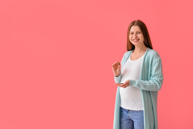 Беременная молодая женщина с таблетками на цветной поверхности Premium Фотографии