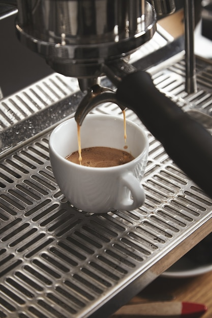 カフェショップの大きなイタリアのマシンでコーヒーを準備します。閉じる 無料写真