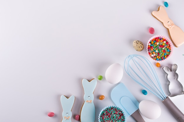 Preparation of gingerbread cookies. easter cookies in the shape of  a  funny  rabbit , tools necessary to make gingerbread pastry, colored sprinkles. easter concept. Premium Photo